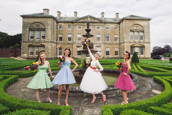 Bride and bridesmaids posing in front of Sledmere House fountain