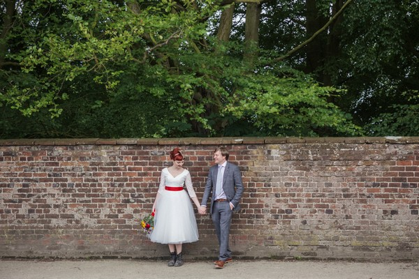 Bride and groom holding hands in front of wall