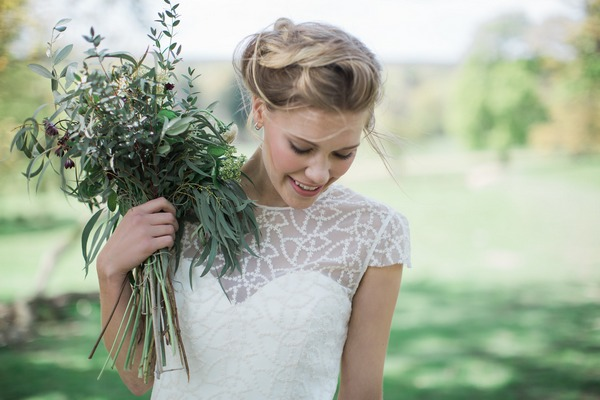 Bride holding bouquet to shoulder