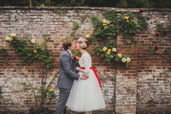 Bride and groom kissing in front of wall