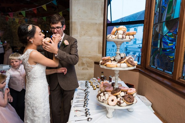 Bride and groom eating doughnuts