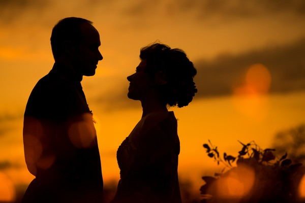 Silhouette of bride and groom against orange sky