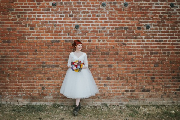 Bride standing against wall