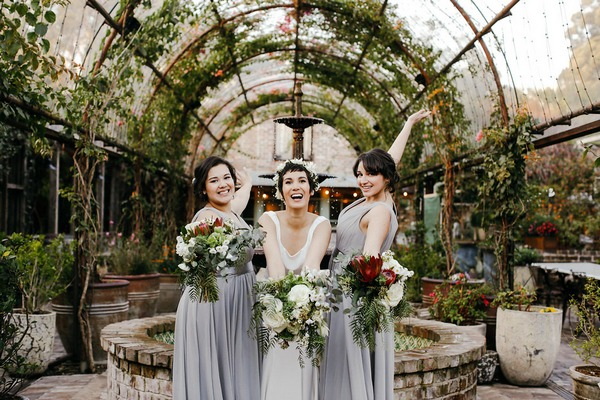 Bride and bridesmaids holding out bouquets