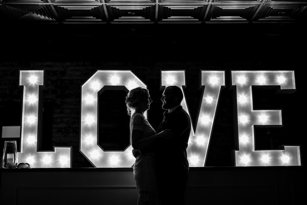 Bride and groom dancing in front of LOVE letters