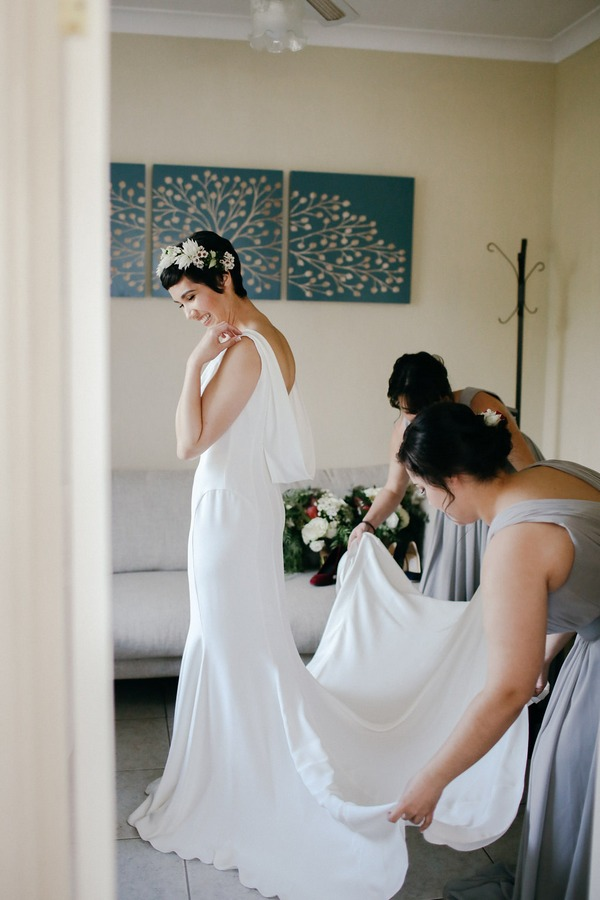 Bridesmaids pulling out bride's train