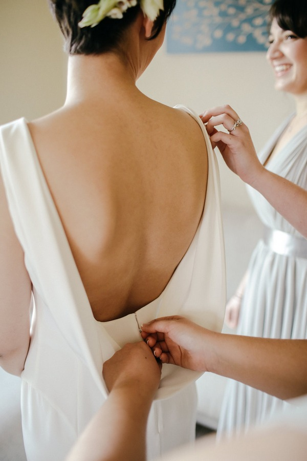Back of bride's wedding dress being fastened