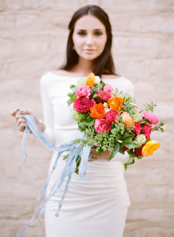 Bride holding brightly coloured bouquet