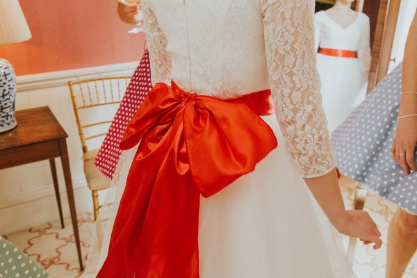 Large red bow on back of bride's wedding dress