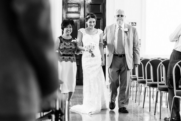 Mother and father walking bride down the aisle