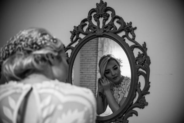 Bride looking in mirror to put earrings on