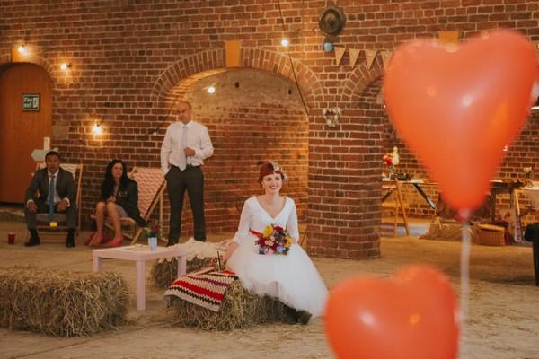 Bride sitting on hay bale listening to speech