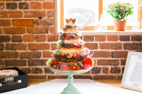 Naked wedding cake with fruit and colourful flowers