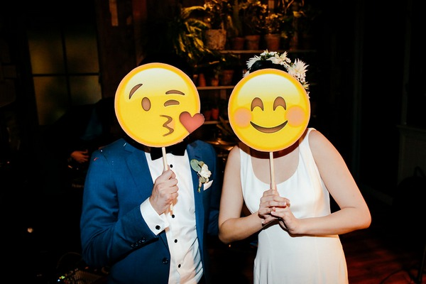 Bride and groom holding emoji face masks over their faces