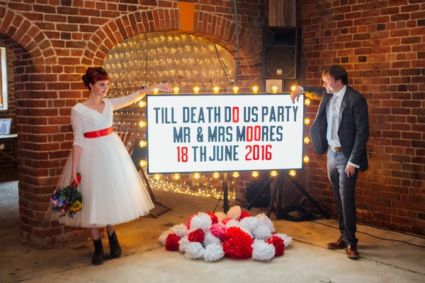 Bride and groom standing next to Till Death Do Us Party illuminated sign