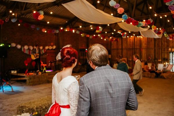 Bride and groom standing listening to wedding guitarist