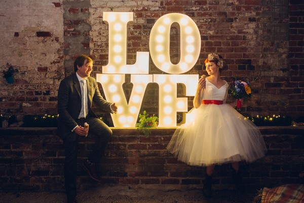 Bride and groom sitting next to illuminated LOVE letters