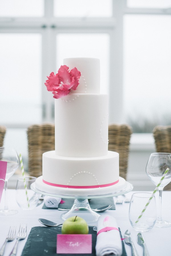 Wedding cake with pink flower and ribbon