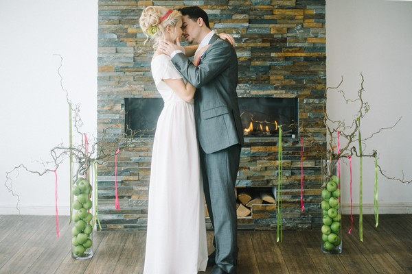 Bride and groom kissing in front of fireplace