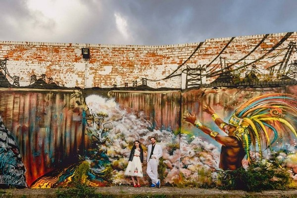 Bride and groom standing gainst graffiti wall - Picture by Lisa Carpenter Photography