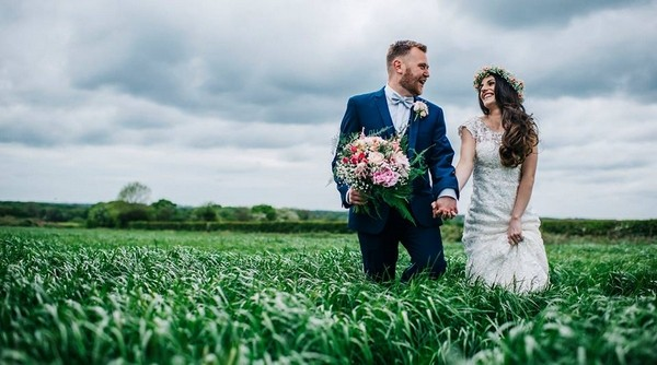 Bride and groom in field with groom holding bride's bouquet - Picture by Kerry Woods Photography
