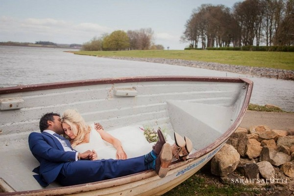 Bride and groom laying down in rowing boat - Picture by Sarah Salotti Photography