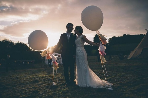 Bride and groom holding balloons as the sun sets - Picture by Naomi Jane Photography