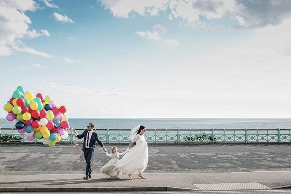 Bride and groom on seafront holding flower girl's hand and colourful balloons - Picture by Dragan Zlatanovic Wedding Photographer