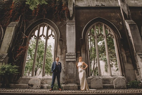 Bride and groom standing in front of ruin wall - Picture by Emma-Jane Photography