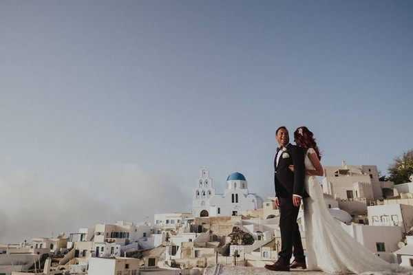 Bride and groom with the backdrop of Santorini - Picture by Steve Fuller Photography
