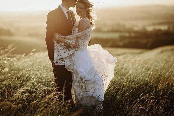 Bride and groom in field in hazy sunshine - Picture by Green Antlers Photography