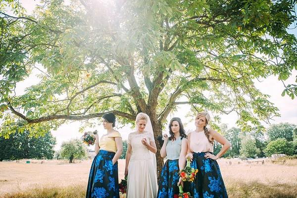 Bride and bridesmaids posing under tree