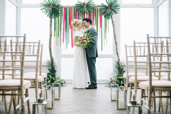 Bride and groom in front of pink and green wedding backdrop