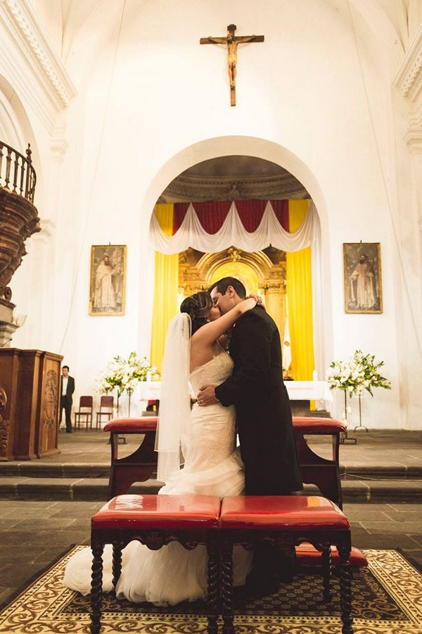 Bride and groom kiss in La Merced church in Guatemala