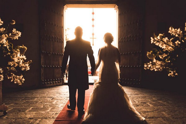 Silhouette of bride and groom walking out of wedding ceremony in La Merced church in Guatemala