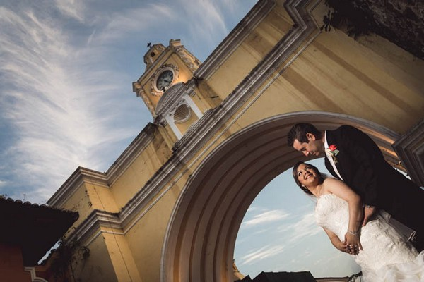 Bride and groom under Santa Catalina Arch and clock tower in Guatemala