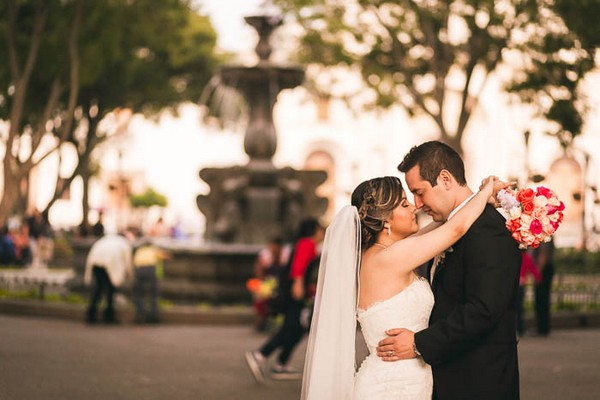 Bride and groom with fountain in background