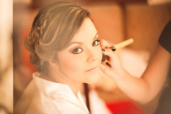 Bride looking at camera as she has make-up done