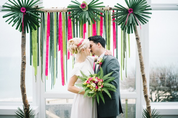 Bride and groom kissing in front of pink and green backdrop