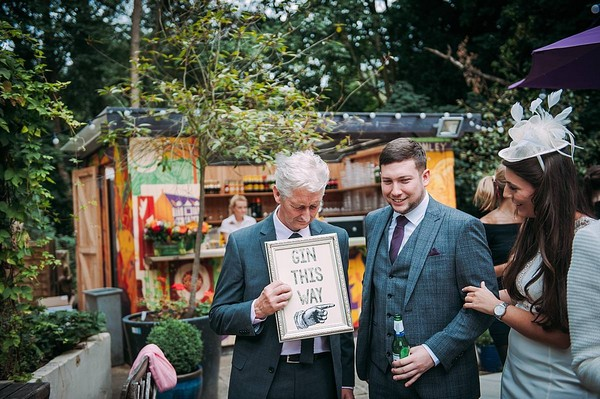 Wedding guest holding gin sign