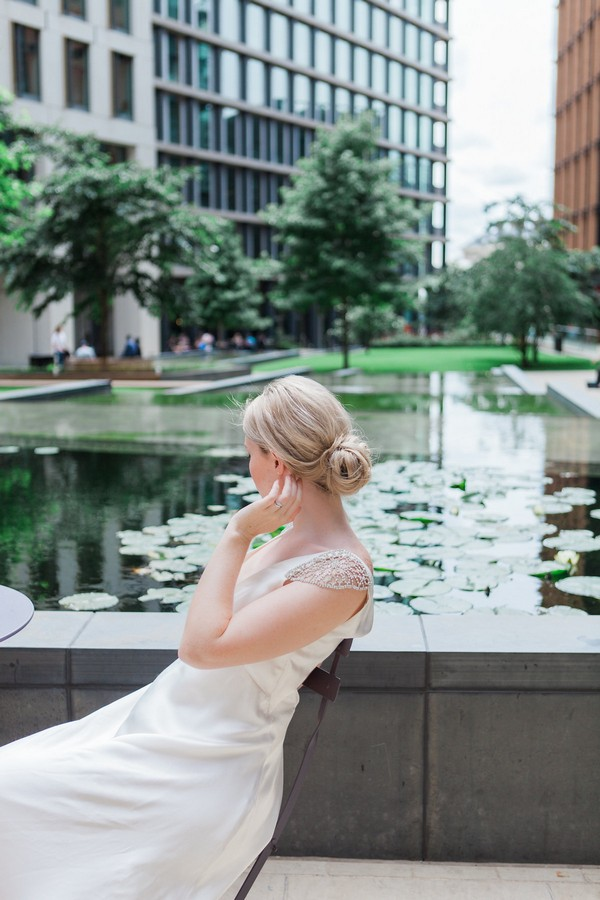 Bride sitting next to water feature in London