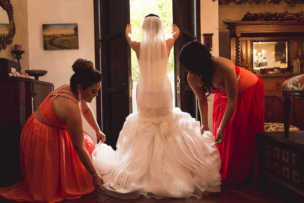 Bride standing at window as bridesmaids pull out train of her dress