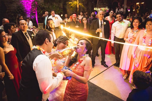 Bride and groom pouring rum into guest's mouth