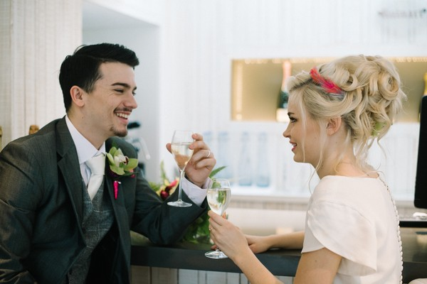 Bride and groom having drinks at bar