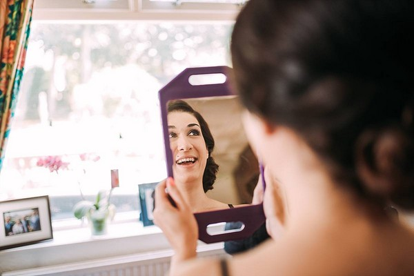 Bridesmaid smiling as she looks in mirror to see make-up