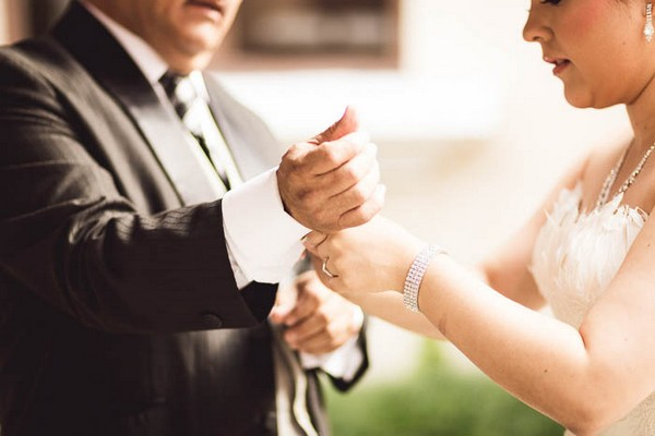 Bride helping father with cufflinks