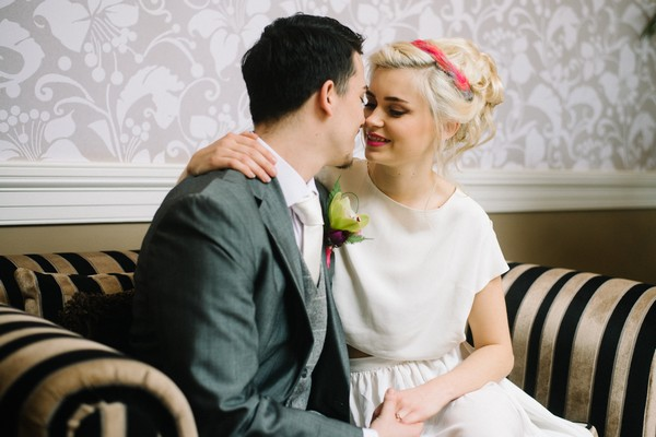 Bride and groom about to kiss on couch