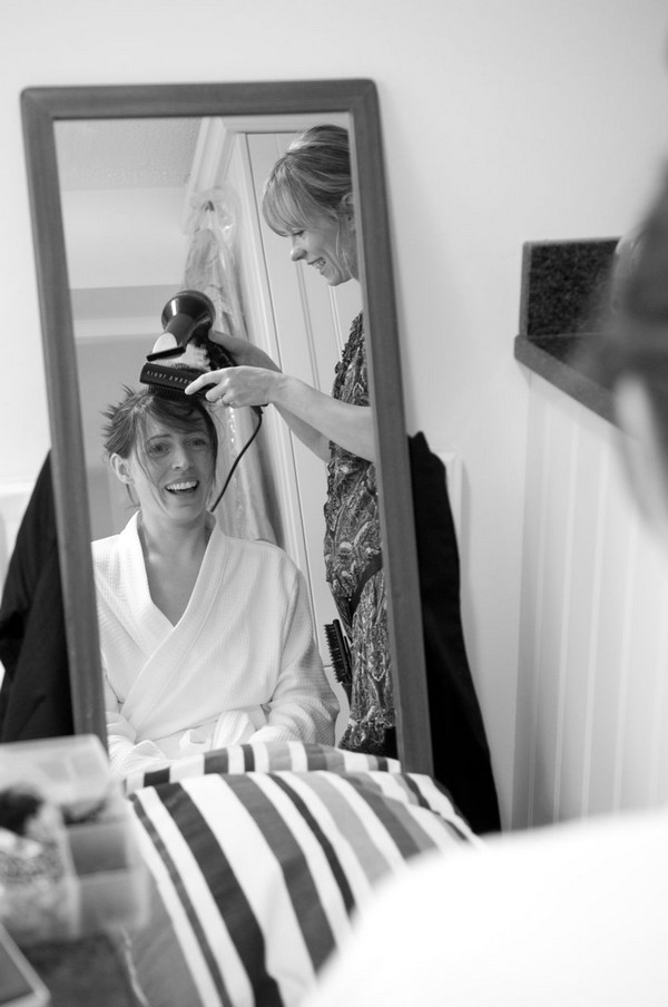 Bride having front of hair blow-dried after washing