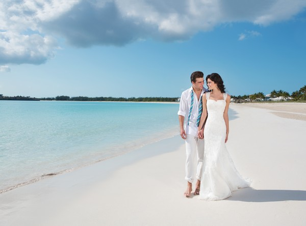 Bride and groom walking on Breezes Bahamas beach