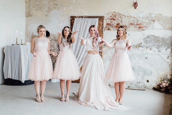 Bride and bridesmaids throwing confetti in the air